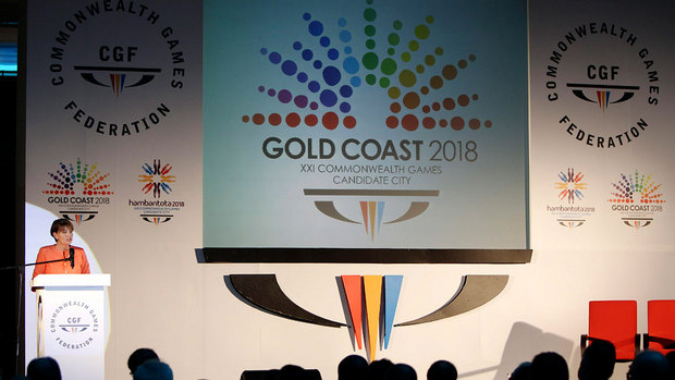 Anna Bligh_in_front_of_Gold_Coast_2018_logo