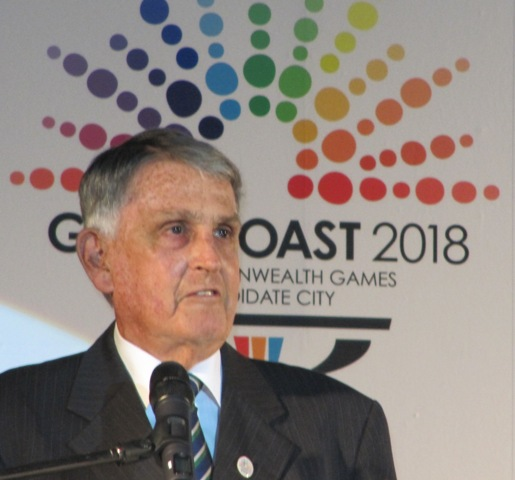 Ron Clarke_in_front_of_Gold_Coast_2018_logo