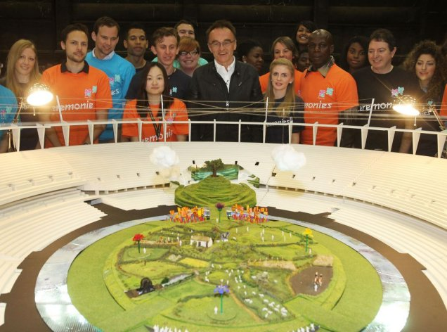Danny Boyle_in_front_of_mock_up_of_Olympic_Stadium_with_volunteers_June_12_2012