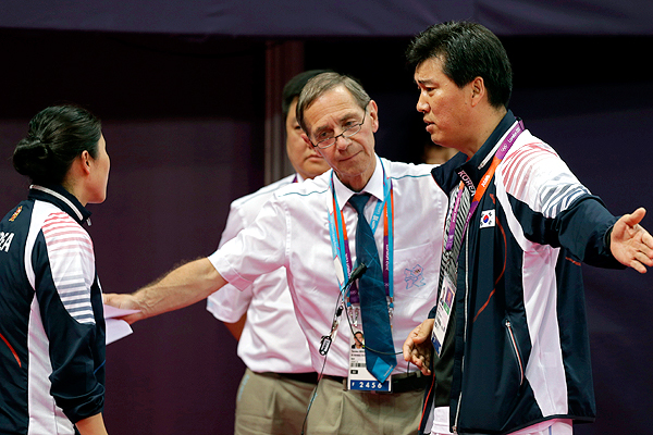 Referee Torsten_Berg_second_from_right_talks_to_South_Korean_coach_Sung_Han-kook_right_after_Berg_issued_a_black_card_to_the_players_in_the_womens_doubles_match_between_South_Korea_and_Indonesia