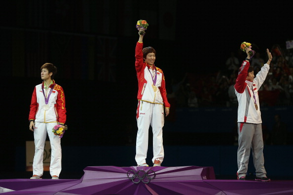 Xiaoxia Li_of_China_stands_on_the_podium_after_winning_the_Gold_medal_Ning_Ding_of_China_L_the_Silver_and_Tianwei_Feng_of_Singapore_R_the_Bronze_following_the_Womens_Singles_Table_Tennis_Gold
