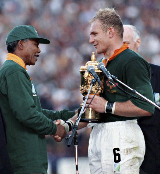 South African president Nelson Mandela dressed in a No 6 Springbok jersey congratulates the Springbok captain Francois Pienaar after South Africa beat the All Blacks by 15-12 to win the 1995 Rugby World Cup
