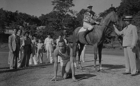 Jesse Owens poses next to race horse