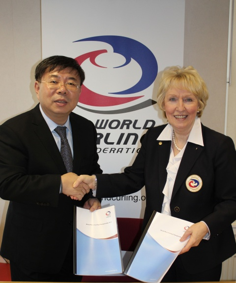 Chinese Curling Association President Ni Huizhong and WCF President Kate Caithness with the contracts for the WMCC 2014