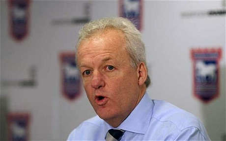 Simon Clegg in front of Ipswich Town logo