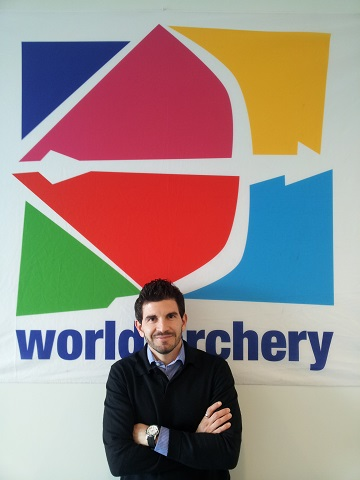Marcos Lorenzo in front of World Archery sign