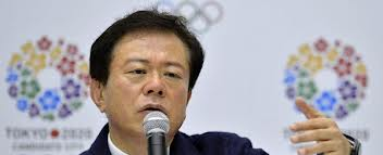 Naoki Inose in front of Tokyo 2020 logo