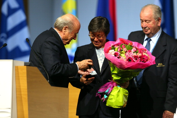 Sepp Blatter presents Moya Dodd with flowers and her FIFA pin