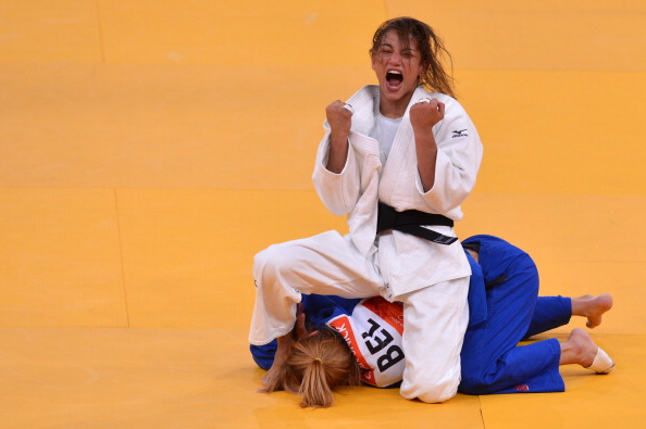 Brazils Sarah Menezes celebrates after winning against Belgiums Charline Van Snick at London 2012