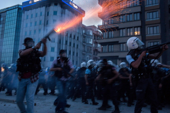 Riot police fire tear gas to disperse the crowd during a demonstration near Taksim Square