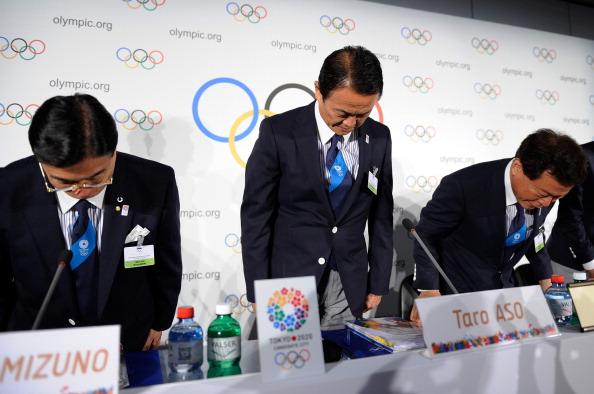 Masato Mizuno Taro Aso and Naoki Inose bow as they acknowledge IOC members in Lausanne
