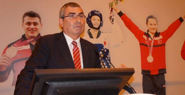 Uğur Erdener in front of Turkish athletes sign