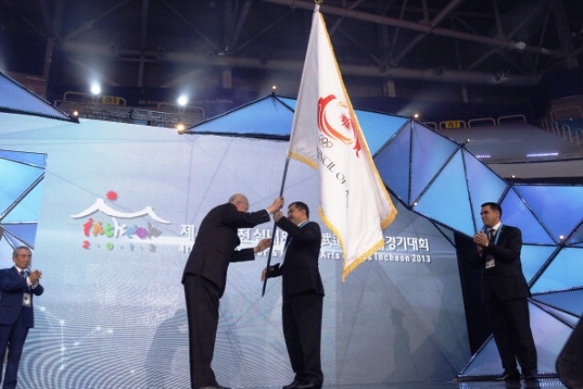 Weiji Zhong L honorary vice President of OCA hand over OCA flag to Orazov Batyr RSports Minister of Turkmenistan during closing ceremony of the 4th Asian