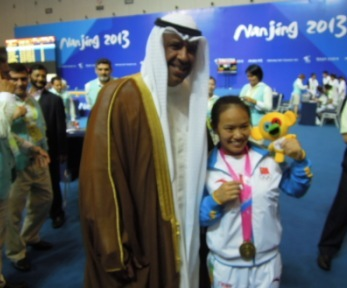 Sheikh Ahmad with the first gold medalist in Nanjing: Chinese weightlifter Huihua Jiang