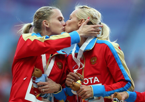World Championship gold medalists Tatyana Firova and Kseniya Ryzhova of Russia kiss on the podium during the medal ceremony for the women's 4x400 metres relay, which some have claimed was a proest against their country's anti-gay laws