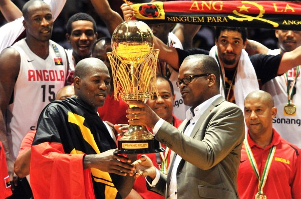 Angola captain Carlos Almeida receives the African Basketball Championship trophy from Ivory Coast sports minister Alain Lobognan
