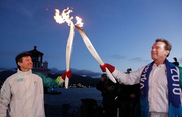 Arnold Schwarzenegger hands the Olympic flame Sebastian Coe ahead of Vancouver 2010
