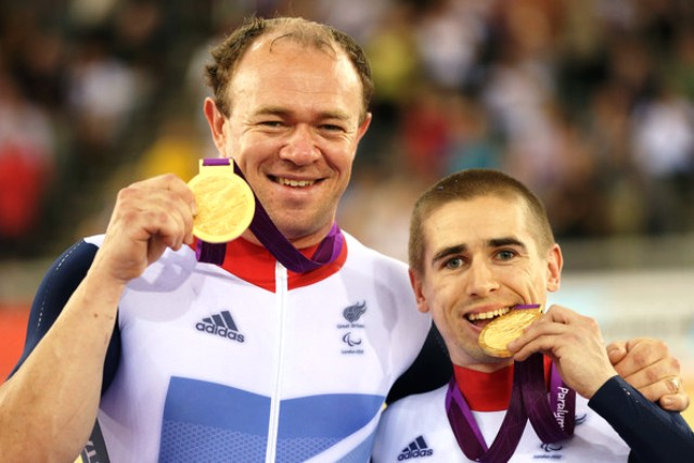 Neil Fachie (right) and partner Barney Storey celebrate their gold medal triumph at London 2012