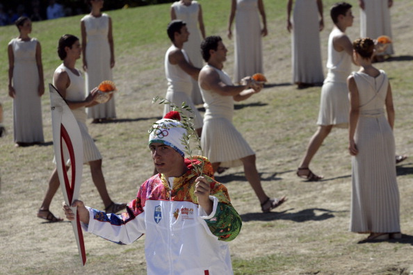 First Olympic Flame torch bearer Greek skier Giannis Antoniou holds the torch and an olive branch before receiving the flame during the final dress rehersal of the Flame Lighting Ceremony for Sochi 2014