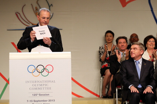 IOC President Jacques Rogge announces that he will be succeeded by Thomas Bach, as the German looks on