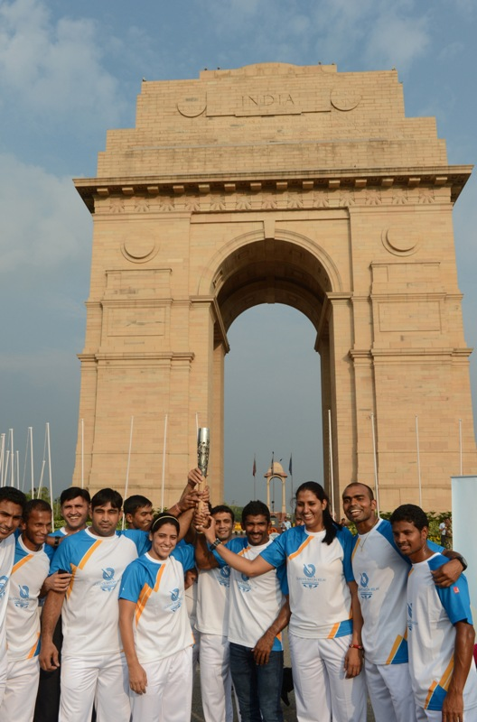 Athletes celebrate the arrival of the Queen's Baton at India Gate in New Delhi