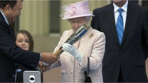 Queen Elizabeth II inspects the Glasgow 2014 baton