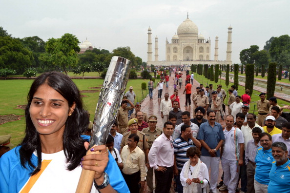 Asian Games 3,000 metres steeplechase champion Sudha Singh holds the Queen's Baton at the Taj Mahal in Agra