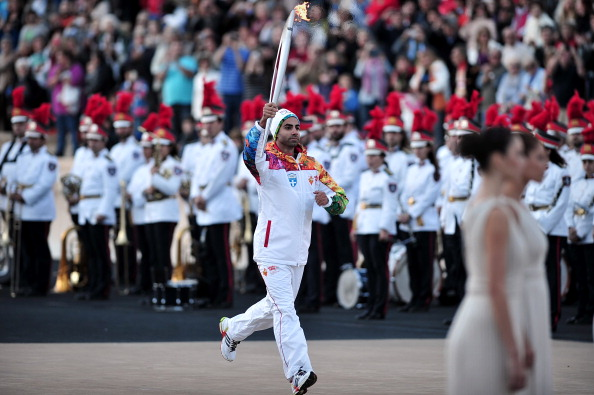 Greek figure skater Panagiotis Markouizos carried the Olympic Torch into the Panathenaic Stadium in Athens before it was handed over to Sochi 2014
