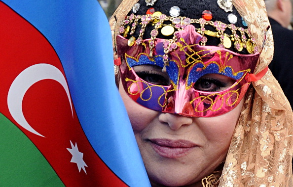 A masked woman holds an Azerbaijani flag as she takes part in the celebration of Navruz, the Central Asia's spring welcome festival, in Baku, the capital of Azerbaijan, on March 19, 2013. © Getty Images