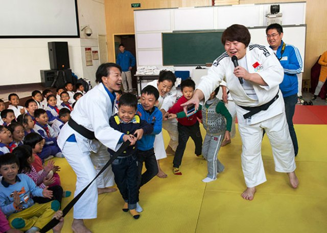 Olympic champion Tong Wen (right) gets children moving on a visit back to her old primary school © IJF Media