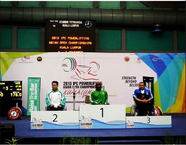 Paralympic champion Yakubu Adesokan (centre) recieves  his gold medal at the IPC Powerlifting Asian Open Championships