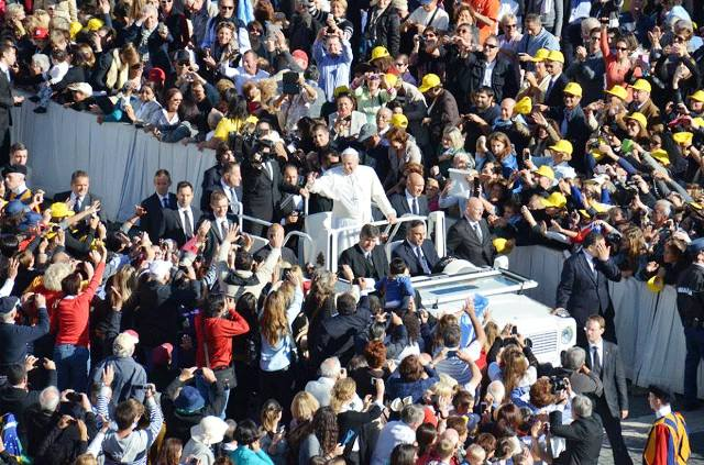 Pope Francis is greeted by large crowds in St Peters Square before officially lighting the Trentino 2013 torch