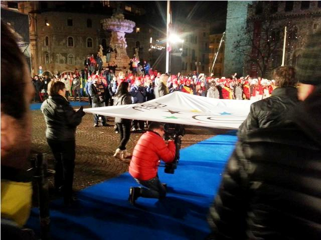 The FISU flag makes its way through the crowds in the Piazza Duomo