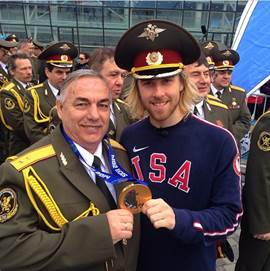 "First gold medal winner Sage Kostenburg was ""super stoked"", I would assume, to pose with a Russian guard"