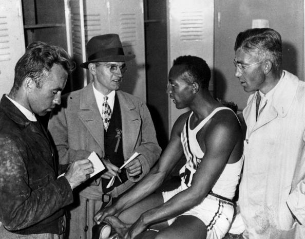Jesse Owens, winner of four golds at the 1936 Berlin Olympics, is interviewed during the Games by the press. His own story about being snubbed by Hitler, however, came about by popular demand rather than because it was true - as Wallechinsky notes ©Hulton Archive/ Getty Images