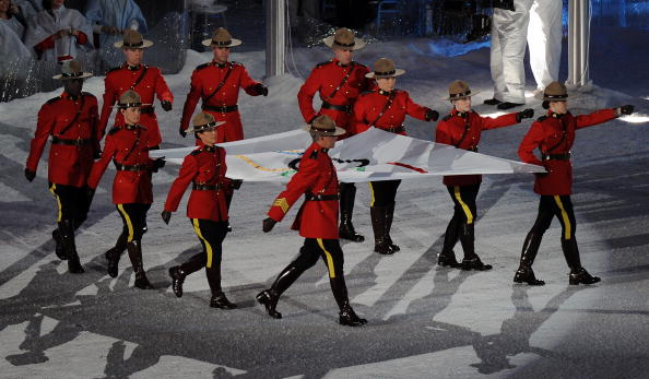 The Royal Canadian Mounted Police troop the Olympic flag from the arena during the Vancouver 2010 Closing Ceremony ©AFP/Getty Images