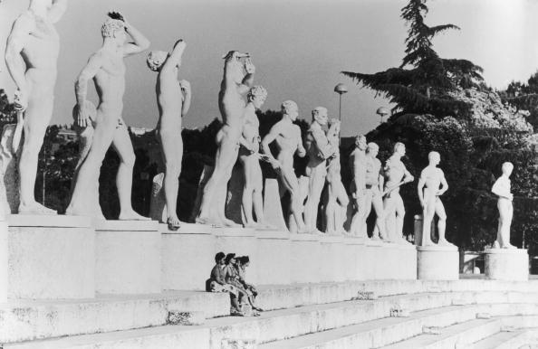 A group of women sit beneath statues at the Olympic Stadium before the Rome 1960 Olympics, to which David Wallechinsky was taken by his father, Irving Wallace. Wallechinsky-style detail: the statues were originally put up by Mussolini but had been declared indecent by the Italian Church ©Hulton/ Getty Images