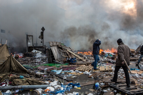 Anti-government protesters walk amid debris and flames near the perimeter of Independence Square ©AFP/Getty Images