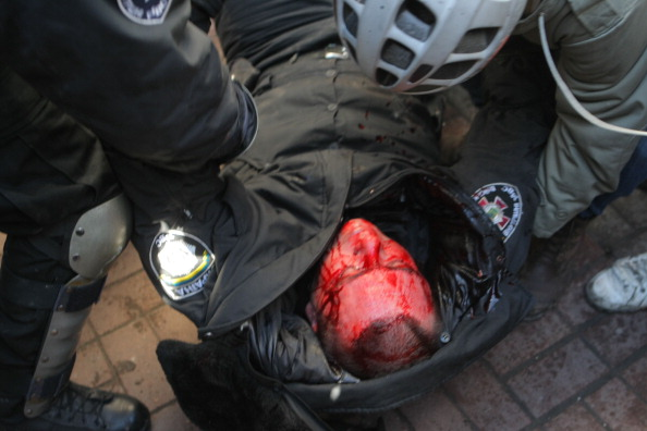 An injured Ukrainian riot police is carried by his collegaues during the clashes between anti-Government protestors and riot police at Independence Square in Kiev ©AFP/Getty Images