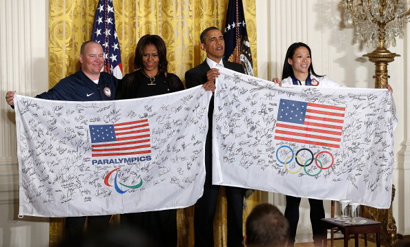 Barrack and Michelle Obama receiving autographes flags from the US Olympic and Paralympic teams ©Getty Images