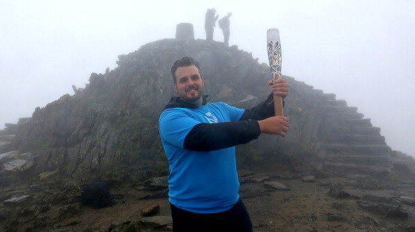 Aled Davies held the Glasgow 2014 Queen's Baton aloft at the summit of Snowdon in Wales ©Getty Images