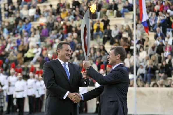 Spyros Capralos (left) hands over the Olympic Torch for Sochi 2014 at Panathenaic Stadium in Athens to Russian Deputy Prime Minister Dmitry Kozak ©Getty Images