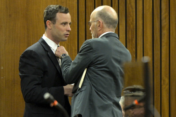 Arnold, Oscar Pistorius' uncle, helps the Paralympic athlete with his tie during today's proceedings in court ©Getty Images