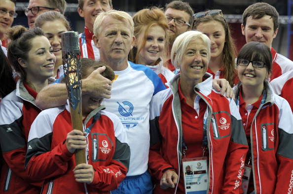 """Scottish national football manager Gordon Strachan poses with the Queen's Baton alongside """"Games Makers"""" at Hampden Park ©Getty Images"""