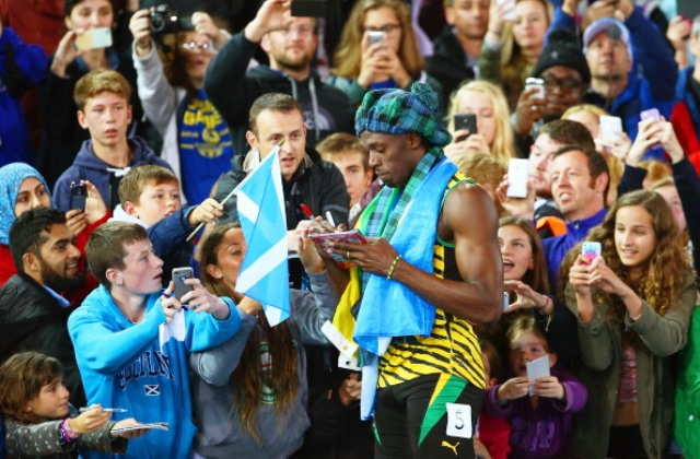 Fans scramble for an autograph from Usain Bolt at Hampden Park, one of the biggest attractions at Glasgow 2014 ©Getty Images