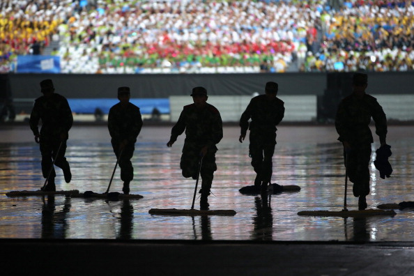 Soldiers helped remove water from the centre of the stadium as rain lashed Nanjing ©Getty Images