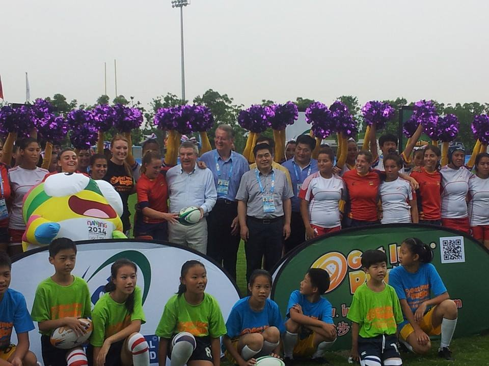 Thomas Bach alongisde IRB President Bernard Lapasset and a multitude of fans, dancers and rugby sevens players ©ITG