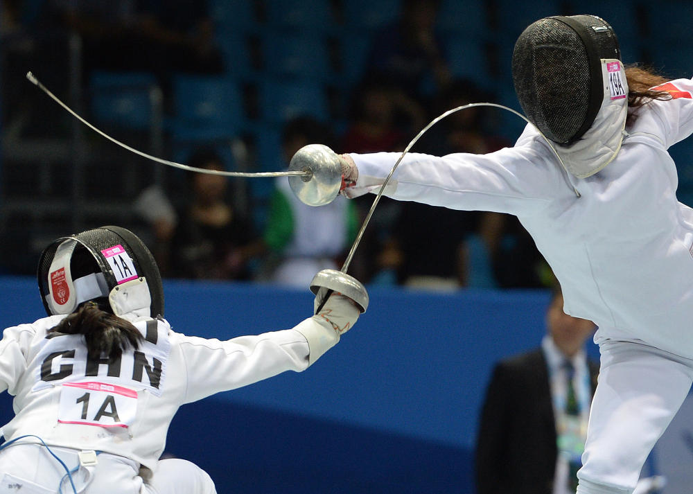 Zhong Xiuting (left) of China went up against Valeriia Uvarova of Kyrgyzstan in the fencing round of the mixed international team relay event of the modern pentathlon competition ©Nanjing 2014