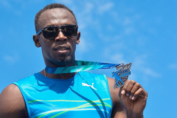 Usain Bolt shows off his medal for winning the Mano a Mano 100m challenge on Copacabana Beach last weekend. He has now ended his season early ©Getty Images