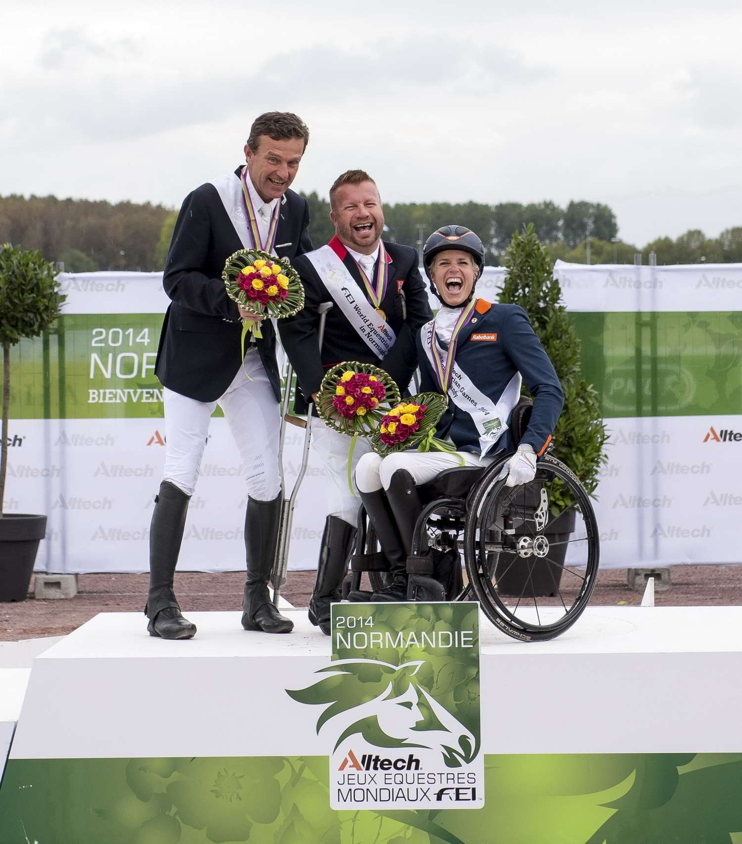 Lee Pearson (centre) celebrates clinching the Grade Ib individual title at the World Equestrian Games ©FEI